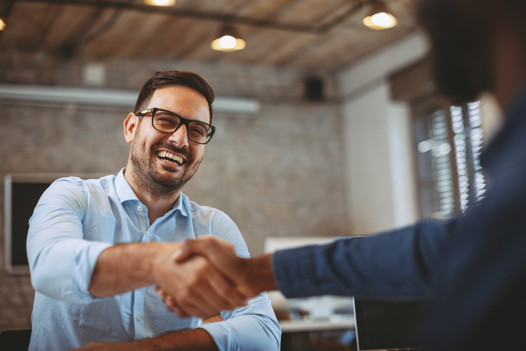 Man shaking hands with organisations stakeholder after discussing HR initiative